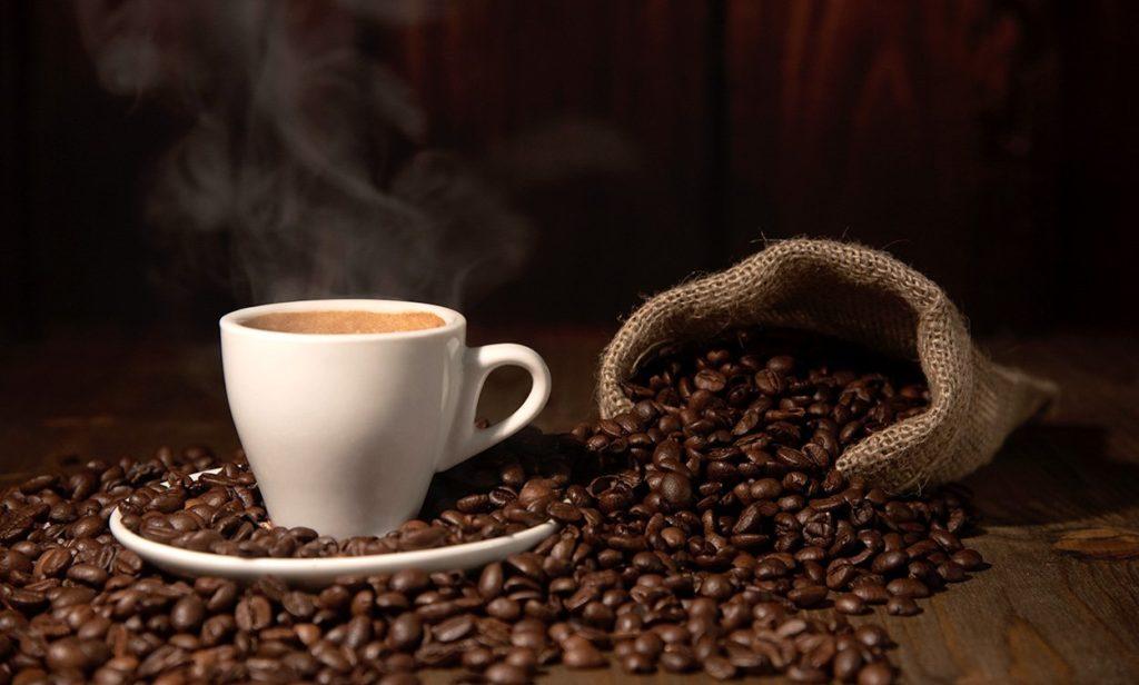Frischer Kaffee und geröstete Kaffeebohnen in einem umgekippten Sack