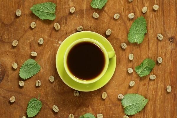 Grüner Kaffee (gekocht) in einer grünen Tasse auf einem Holztisch mit rohen Kaffeebohnen und grünen Blättern