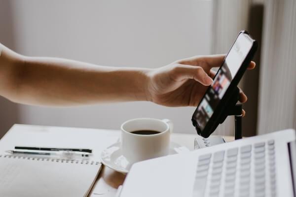 Kaffee am Arbeitsplatz mit Laptop und Handy