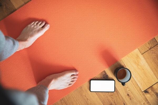 Füße stehen auf Yogamatte daneben Handy und Kaffeetasse