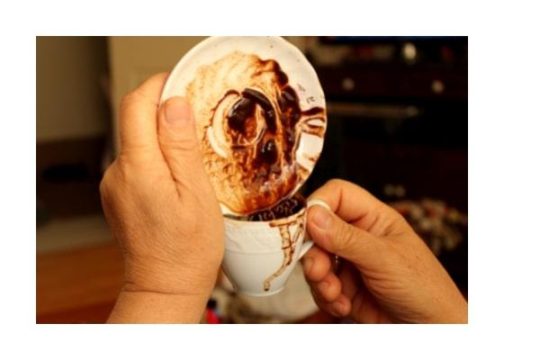Untertasse mit Kaffeesatz und Kaffeesatz läuft in die Tasse