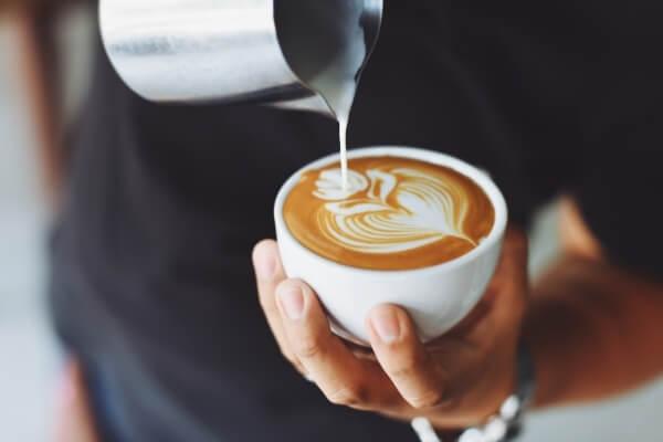 Latte Art - Milch wird kunstvoll in einen Cappuccino gegossen