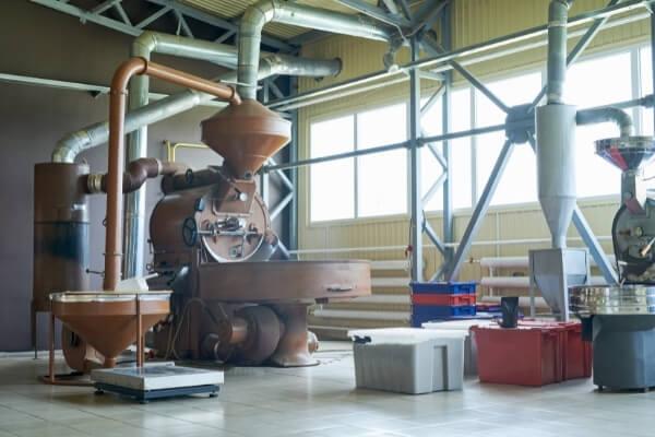 Kaffee-Röstraum mit großer Trommelröstmaschine und der gesamten dazugehörigen Technik