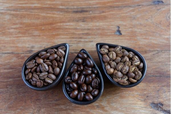 braune, dunkelbraune und hellbraune Kaffeebohnen in drei verschiedenen Schälchen