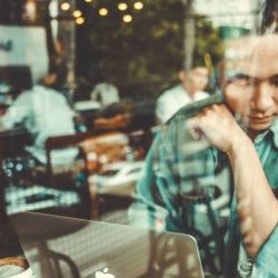 Mensch mit Laptop in Café