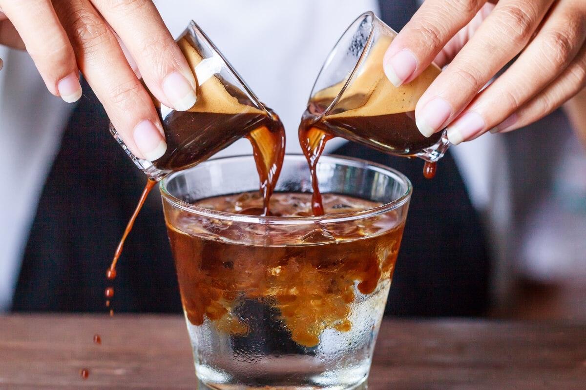 Zwei Espresso werden in ein Glas Wasser gekippt