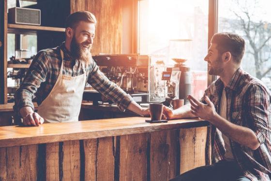 Barista steht an der Bar und lächelt einen Kunden an