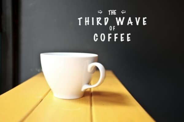 """Kaffeetasse auf Holztisch mit Schrift """"Third Wave Coffee"""" im Hintergrund"""