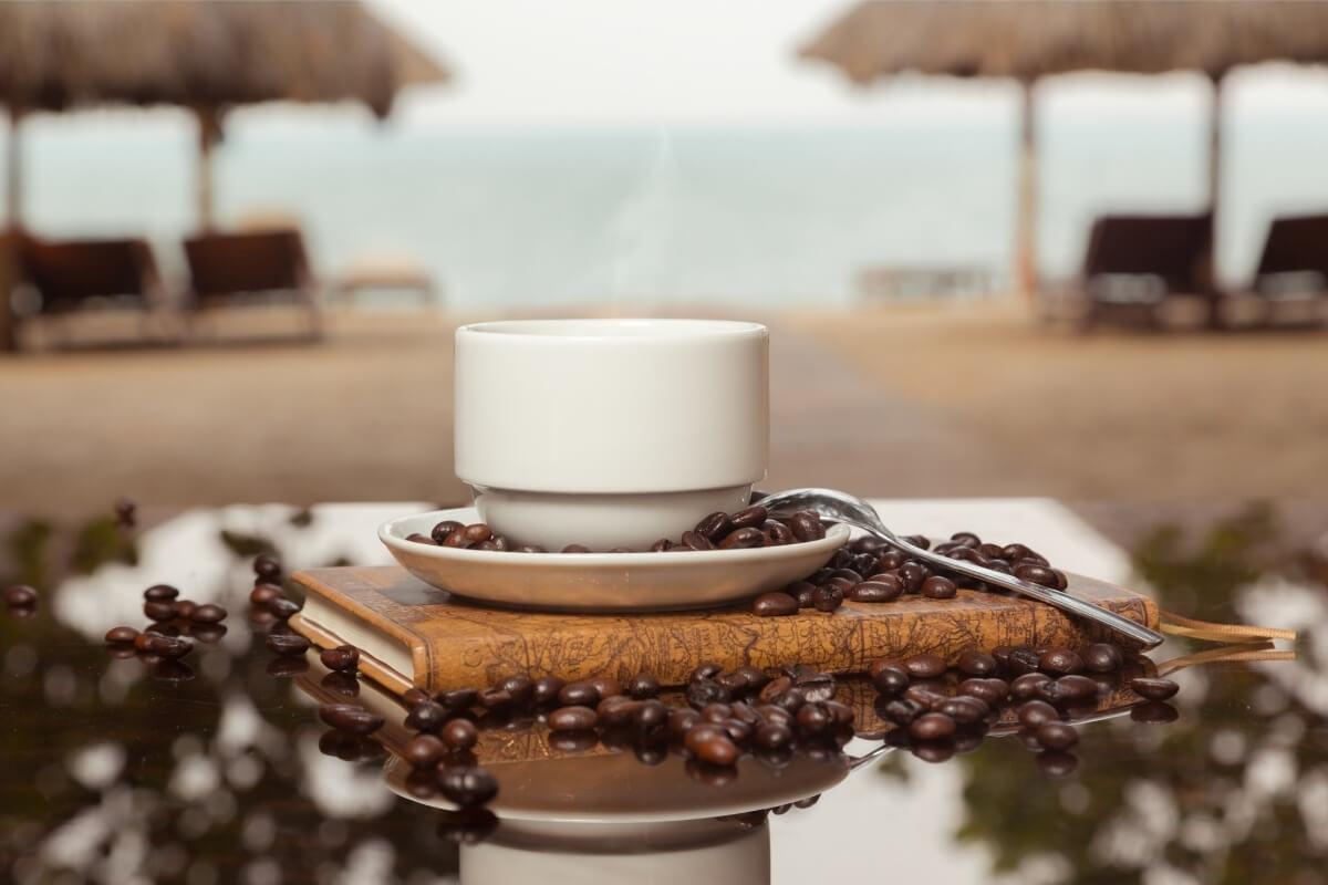 Kaffee in einer Tasse auf einem Tisch am Strand