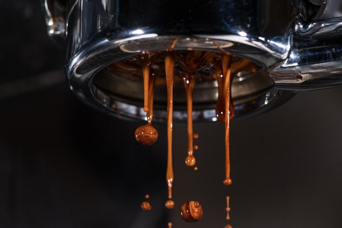 Espresso tropft aus bodenlosem Siebträger