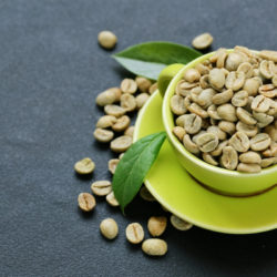 Grüne, ungeröstete Kaffeebohnen in grüner Tasse