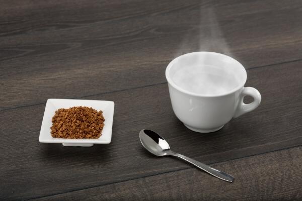 Instantkaffee in Form von Granulat in einem weißen Schälchen, daneben ein Kaffeelöffel und eine weiße Tasse mit heißem Wasser auf einem dunklen Holztisch