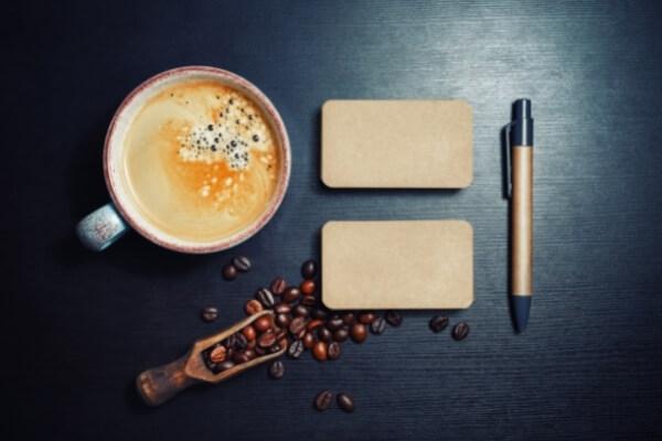 Kaffeetasse und Kaffeekirschen mit Stift und Block aus Vogelperspektive