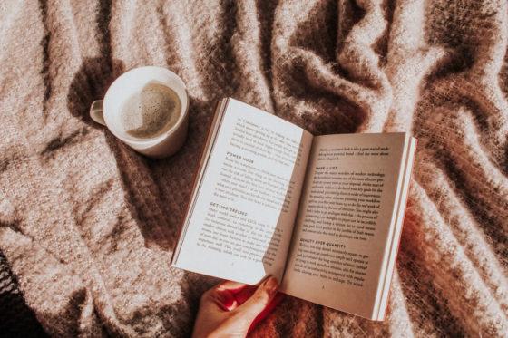 Kaffee Creme und ein Buch auf einer Decke