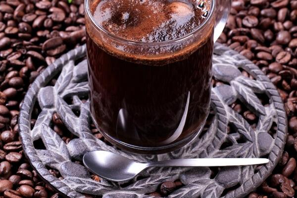 Schwarzerer Kaffee im Glas und Kaffeebohnen im Hintergrund