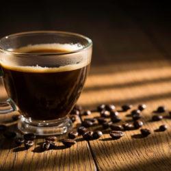 Schwarzer Kaffee mit Kaffeebohnen daneben im Licht und Schattenspiel auf einem Tisch
