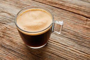 Kaffeetasse aus Glas mit purem Kaffee gefüllt auf Holzuntergrund