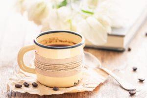 Kaffeetasse aus Emaille auf Holtisch mit zugeklapptem Buch und Blumen im Hintergrund