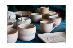 Keramik Kaffeetassen und verzierte Untertasse auf dunklem Untergrund