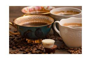 4 Kaffeetassen unterschiedlicher Form und Farbe mit Kaffeebohnen auf Tisch